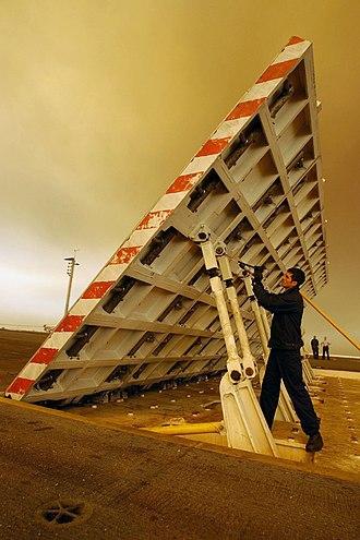Jet blast deflector - An airman services a jet blast deflector (JBD) before flight operations aboard an aircraft carrier