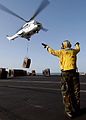 US Navy 040527-N-7871M-047 Aviation Boatswain's Mate 2nd Class Francis Gardner, of Waukegan, Ill., directs an Aerospatiale SA330 Puma helicopter after picking up a pallet of supplies.jpg