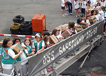 Girl Scouts and Brownies from two troops in Singapore pass Girl Scout cookie boxes up the brow of the rescue and salvage ship USS Safeguard (ARS 50) as part of Operation Thin Mint.