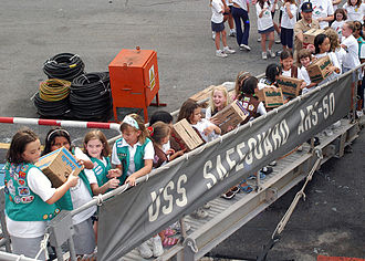 American Scouting overseas - Girl Scouts and Brownies from two troops in Singapore pass Girl Scout cookie boxes up the brow of the rescue and salvage ship USS Safeguard (ARS 50) as part of Operation Thin Mint.