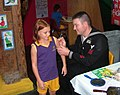 US Navy 060827-N-3609W-002 Personnel Specialist 1st Class John Long applies some nautical art to a New Orleans youth's arm.jpg