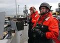 US Navy 070307-N-5416W-004 Gunner's Mate 2nd Class Lucas Friend and Gunner's Mate 3rd Class Derek Benedict stand watch with a .50-caliber machine gun aboard Nimitz-class aircraft carrier USS Theodore Roosevelt (CVN 71).jpg