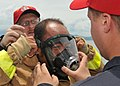 US Navy 100812-N-3215T-134 Sailors assigned to the guided-missile destroyer USS John S. McCain (DDG 56) help a Vietnam People's Navy sailor put on a firefighting facemask during a damage control demonstration.jpg