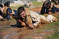 US Navy 110203-N-2531L-282 Hospital Corpsman 1st Class Michael Astorga crawls through a mud pit during a tactical combat casualty care field exerci.jpg