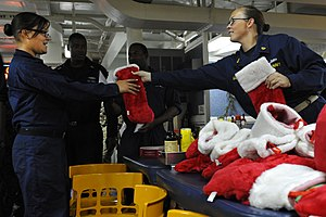 US Navy 111222-N-KS651-091 Personnel Specialist Chief Janna Mason hands out Christmas stockings to single Sailors on the mess decks of dock landing.jpg
