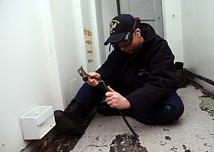 US Navy 120214-N-ZT599-003 Aviation Boatswain's Mate (Fuels) Airman Ashlie Gack uses a hammer and chisel to remove tile aboard the nuclear-powered.jpg