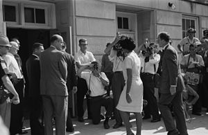 Racism - African-American university student Vivian Malone entering the University of Alabama in the U.S. to register for classes as one of the first non-white students to attend the institution. Until 1963, the university was racially segregated and non-white students were not allowed to attend.