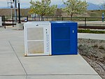 White & blue bicycle lockers at 5600 W Old Bingham Hwy station, Apr 16.jpg
