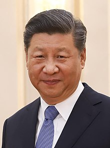 Head shot of Xi Jinping in 2019. He is wearing a black suit jacket, white shirt and a blue necktie.