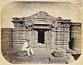 1871 photo of the ruins of a Kali Hindu temple at Chintarian, Devikot in Bangladesh with Robert Gill seated.jpg