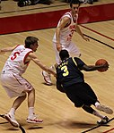 A basketball player in a dark blue uniform is dribbling past a defender in white.