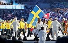 Photo de l'équipe de Suède qui défile lors de la cérémonie d'ouverture des Jeux olympiques, Forsberg en tête portant le drapeau suédois.