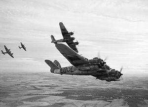 Four twin-engined World War II-era monoplanes in flight over farmland