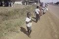 ASC Leiden - F. van der Kraaij Collection - 01 - 036 - Children alongside Tubman Boulevard. A motorbike, cars - Monrovia, Old Road, Montserrado County, Liberia, 1977.tiff