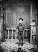 A young boy standing and holding a book NLW3364971.jpg