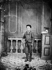 A young boy standing and holding a book