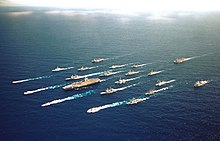Aerial photograph of twenty-one ships, including an aircraft carrier, sailing in close formation.