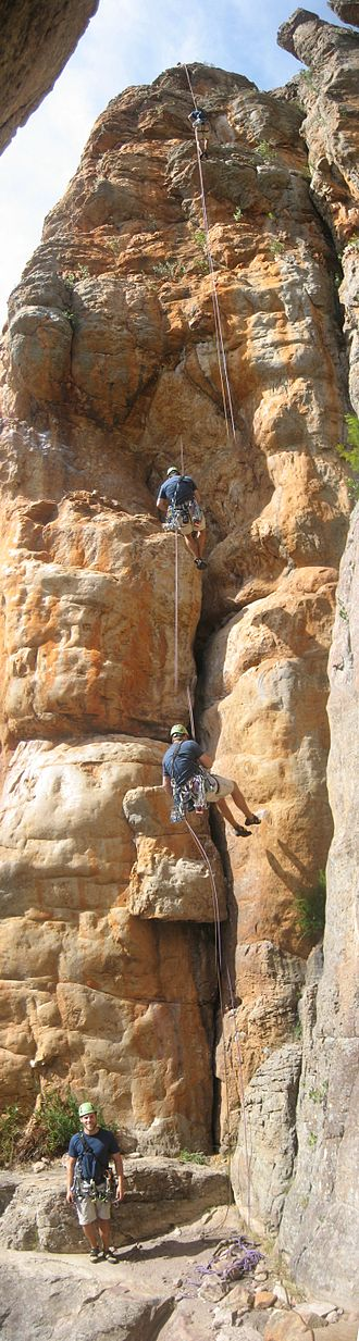 Abseiling - A time-lapse panorama of a rock climber abseiling off a climb