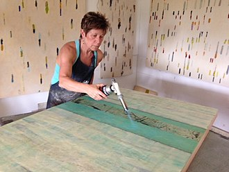 Tracey Adams (painter) - Adams in studio working with molten, pigmented beeswax and torches