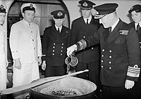 Admiral Sir Bruce Fraser pouring the rum into the Christmas pudding mix on board HMS DUKE OF YORK, November 1943. A20183.jpg