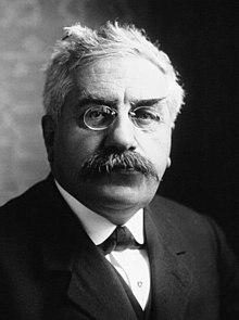 Fotografia frontal de um homem de óculos e bigode.