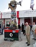 Ambassador Cretz Stands by Fist Crushing a U.S. Fighter Plane Sculpture.jpg