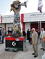 Ambassador Cretz Stands by Fist Crushing a U.S. Fighter Plane Sculpture.jpg