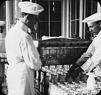 Two men in white, one arranging milk bottles