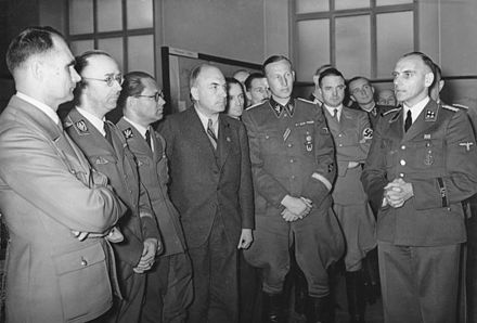 "Heinrich Himmler, Rudolf Hess, and Reinhard Heydrich listening to Konrad Meyer at a Generalplan Ost exhibition, 20 March 1941 Bundesarchiv Bild 183-B01718, Ausstellung ""Planung und Aufbau im Osten"".jpg"