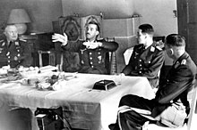 Black-and-white photograph of four men wearing uniforms sitting on wooden chairs around a table in a living room. An older man is sitting at the head of the table on the left. Two younger men are sitting along the table's side, with their backs toward a tiled fireplace on the room's far wall. A fourth man is sitting at the head of the table on the right, leaning back, his left leg folded over his right. The table is covered by a white table cloth. The right-hand side of the table is empty, except for a large dark ashtray, a spoon and an empty glass; the left and centre of the table is covered by an assortment of empty plates, coffee cups and other dishes; there is also a bowl of fruit. The second man from the left has his hands raised, palms facing the camera, and the fingers of both hands pointing to the left of the image. The heads of the three other men are turned toward him.