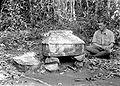 COLLECTIE TROPENMUSEUM Een Europese man zit naast een heilige steen in de vorm van een huisje en rookt een sigaret TMnr 10001095.jpg