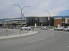 "A road that contains vehicles parking along it, with a ""Kelowna International Airport"" sign in the background, as well as a building for an airport."