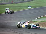 Christian Fittipaldi - Footwork FA15 leads Eddioe Irvine - Jordan 194 at the 1994 British Grand Prix (32500438846).jpg