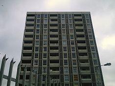 Onze étages d'une tour résidentielle grise, avec une clôture à pointes et une lampe au premier plan.