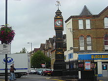 The Clock Tower in South Norwood. It stands on a traffic island. It is a black cast-iron tower, with gilt decoration. The clock face surround is red, with the face being white, with black hands and figures. At the top of the tower is a wind-vane, featuring an arrow and the cardinal compass directions.