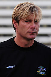 A man with blonde hair who is wearing a black top.