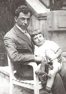 A man sitting on a chair with a small boy on his lap, the boy is hold a small toy dog, both are looking towards the viewer