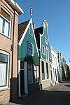 foto van Huis met houten topgevel boven een gepleisterde bakstenen pui