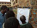 Des électeurs parcourent les listes électorales dans un centre de vote (Collège Alfajiri) à Bukavu 2 (6424786439).jpg