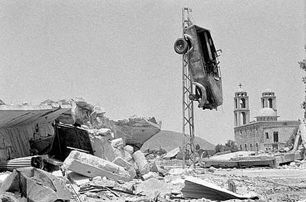 Quneitra village after Israeli shelling, showing a church and an elevated car Destruction in the al-Qunaytra village in the Golan Heights, after the Israeli withdrawal in 1974.jpg