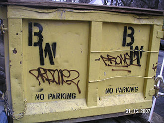 Aerosol paint - Spray paint graffiti tags on a dumpster with the owner's markings spray painted using a stencil. New York City, 2007.