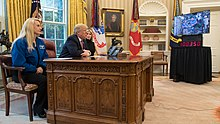 Donald Trump sitting behind the desk with a large screen infront of it