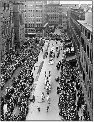 Eaton's Annex - The Eaton's Santa Claus Parade, 1925, with views of City Hall (left) and the Main Store (right) in the foreground, the Eaton's Annex (behind City Hall) in the middleground, and Eaton's factory buildings in the background.