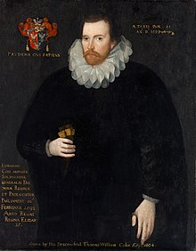 "A portrait of a brunette man in his 40s, with a brunette beard and mustache. He is wearing a shapeless black robe and a Jacobean ruff; to the right of his head is a coat of arms with a motto underneath it. On the bottom right of the portrait is a paragraph of indistinguishable text, while the entire picture is captioned ""Given by the descendent Thomas William Coke 1780+""."