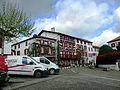 Espelette - rue avec façades de maisons où pendent des cordes de piments.JPG