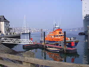 Falmouth, Cornwall - The Falmouth Lifeboat moored by the docks with the old town and The Penryn River in the background