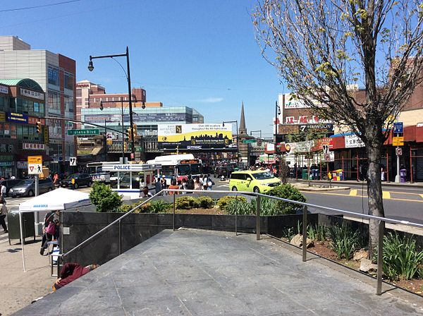 The busy intersection of Main Street, Kissena Boulevard, and 41st Avenue in the Flushing Chinatown (法拉盛華埠), Queens, New York City. The segment of Main Street between Kissena Boulevard and Roosevelt Avenue, punctuated by the Long Island Rail Road trestle overpass, represents the cultural heart of Flushing Chinatown.  Housing over 30,000 individuals born in China alone, the largest by this metric outside Asia, Flushing is home to one of the largest and fastest-growing Chinatowns in the world.[41]