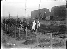 A priest leading soldiers carrying the coffin in a Belgian cemetery. There is a row of wooden crosses in the foreground with a collection of soldiers following the priest in single file.