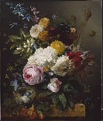 Een boeket bloemen en een vogelnestje op een stenen plint