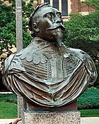 A copper bust of King Gustav Adolph's shoulders and head. He wears his military garb and a crown of laurels. His eyes are fixed at a point in the sky and his chin tilts upward confidently. He wears a full mustache and a triangular goatee. The bust is from Gustavus Adolphus College in Minnesota.